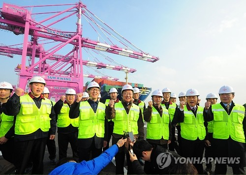 Finance Minister Yoo Il-ho poses for a photo with workers at Incheon's port, a key gateway to South Korea's exports, in this photo dated on Jan. 1, 2017. (Yonhap)