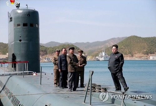 North Korean leader Kim Jong-un (R) is aboard a submarine in this photo released by the North's Rodong Sinmun newspaper on April 24, 2016, watching the launch of a submarine-launched ballistic missile (SLBM). (For Use Only in the Republic of Korea. No Redistribution) (Yonhap)