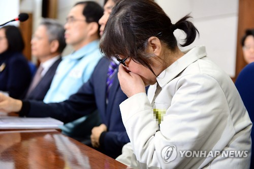 Choi Soon-sil, a longtime friend of President Park Geun-hye who has been indicted on charges of abuse of power and attempted fraud, covers her mouth during her trial at the Seoul Central District Court on Jan. 17, 2017, over an influence-peddling scandal that has led to the president's impeachment. (Pool photo) (Yonhap)