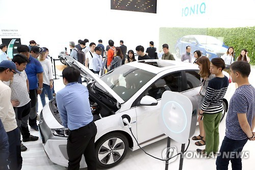 In this photo taken on June 6, 2016, a Hyundai Motor employee explains how the Ioniq all-electric vehicle works during the Busan International Motor Show held in the southern port city of Busan from June 3-12. (Yonhap)
