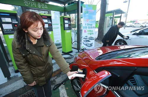 In this photo taken on Dec. 2, 2016, a woman and a man charge their electric cars at a charging station in Gwanghwamun, Seoul. (Yonhap)