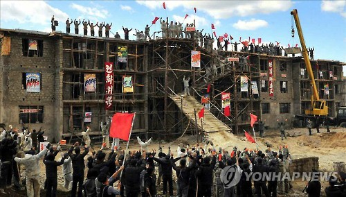 This file photo, taken from North Korean daily Rodong Sinmun on Oct. 14, 2016, shows residents of North Hamgyong Province celebrating the completed construction of new housing in their flood-hit neighborhoods. (For Use Only in the Republic of Korea. No Redistribution) (Yonhap)