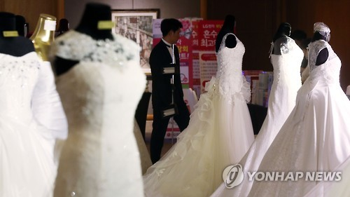 This file photo shows wedding gowns on display in a wedding fair. (Yonhap)