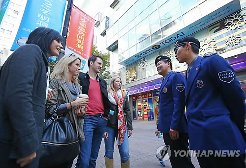 South Korean tourist police listen to foreign tourists in Seoul's Myeongdong district. (Yonhap file photo)