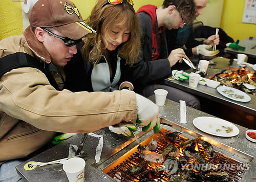 Foreign tourists enjoy food at a restaurant in South Korea. (Yonhap file photo)