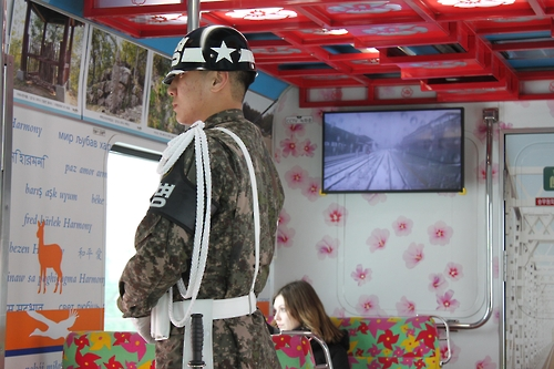 Denise, a German college student, looks through a window in the DMZ Train with a South Korean soldier standing in front of her. (Yonhap)