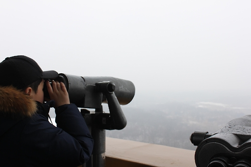 A kid peers at North Korea through binoculars at the Dorasan Observatory. (Yonhap)