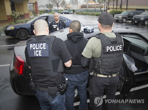 Agents from U.S. Immigration and Customs take an undocumented immigrant to a patrol car in Los Angeles on Feb, 7, 2017, in this photo released by The Associated Press. (Yonhap)