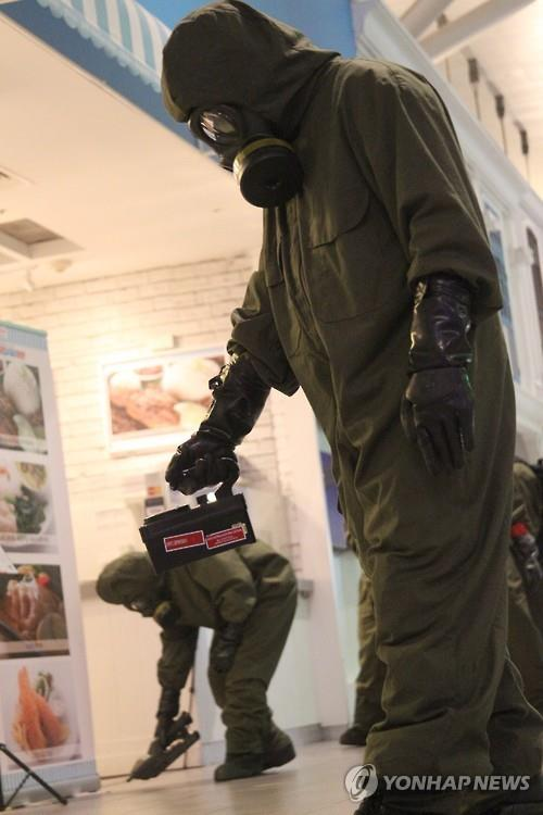 Special personnel wearing protective clothes and masks operate equipment at the departure lobby of Kuala Lumpur International Airport Terminal 2 in Kuala Lumpur on Feb. 26, 2017, looking for any trace of poison. The detection operation was made after VX nerve agent, a lethal chemical weapon, was found on the body of Kim Jong-nam, the murdered half-brother of North Korean leader Kim Jong-un. (Yonhap)