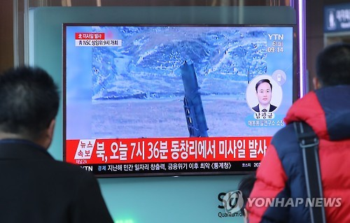 In this photo taken on March 6, 2017, two men watch a news report on North Korea's firing of ballistic missiles into the East Sea early Monday morning. (Yonhap)