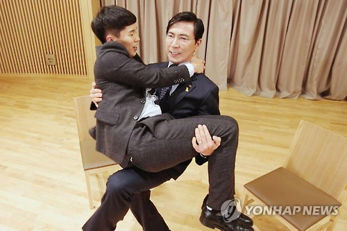 "In this photo provided by SBS Mobydic, Ahn Hee-jung, Democratic Party's presidential hopeful, is seen carrying comedian Yang Se-hyung, host of SBS TV's web-exclusive interview ""Shorterview."" (Yonhap)"