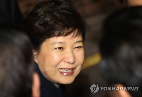 Former President Park Geun-hye smiles in front of her supporters upon her arrival at her private home in southern Seoul on March 12, 2017. (Yonhap)