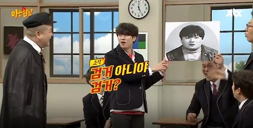 "This image captured from JTBC's variety talk show ""Knowing Bros"" shows Kim Heechul (C) holding up and commenting on an old picture of fellow cast Kang Ho-dong (L). (Yonhap)"
