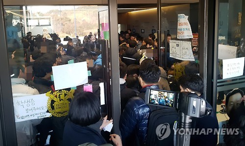 Seoul National University officials attempt to disperse students occupying the school's headquarters on March 11, 2017. Students oppose the school's plan to build a new campus in Siheung, south of Seoul. (Yonhap)