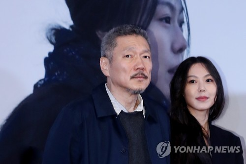 "Hong Sang-soo (L), director of ""On the Beach at Night Alone,"" and its lead actress Kim Min-hee pose for photos during a news conference for the film at a Seoul theater on March 13, 2017. (Yonhap)"