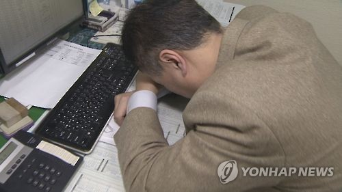 This photo, provided by Yonhap News TV, shows an office worker taking a nap at his office. (Yonhap)