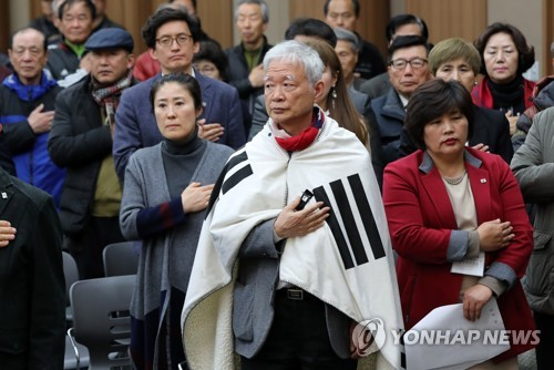 One of Park Geun-hye's lawyers, wrapped in the Korean flag, and other pro-Park citizens meet in Daegu on March 16 to create a regional chapter of the Saenuri Party. (Yonhap)