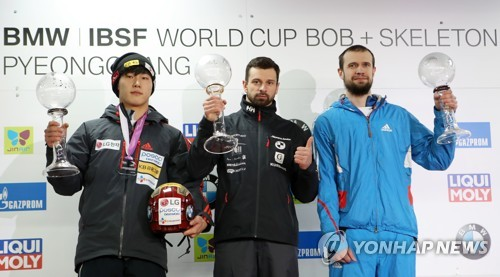 Yun Sung-bin of South Korea (L) holds a trophy for finishing second overall in the men's skeleton for the 2016-17 International Bobsleigh and Skeleton Federation World Cup season at Alpensia Sliding Centre in PyeongChang, Gangwon Province, on March 17, 2017. (Yonhap)