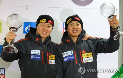 The South Korean men's bobsleigh team of Won Yun-jong (L) and Seo Young-woo hoist their trophies after finishing third overall for the 2016-2017 International Bobsleigh and Skeleton Federation World Cup season at Alpensia Sliding Centre in PyeongChang, Gangwon Province, on March 18, 2017. (Yonhap)