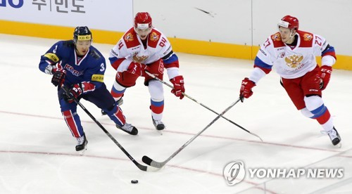 South Korea's Kim Hyun-soo (L) battles Russia's Kirill Semyonov (C) and Viacheslav Leshchenko for the puck during their men's hockey friendly game at Gangneung Hockey Centre in Gangneung, Gangwon Province, on March 19, 2017. (Yonhap)