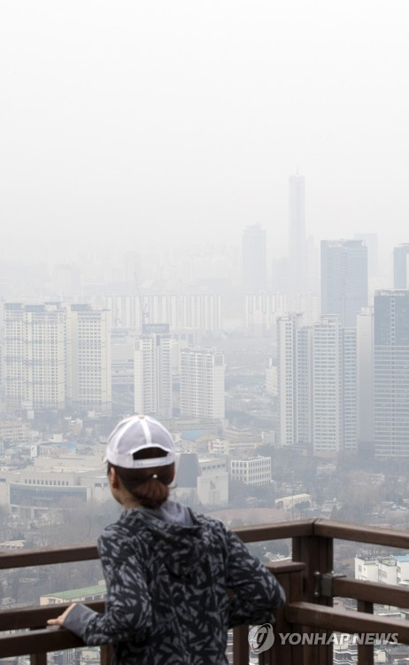 A woman gazes out at downtown Seoul from an observation deck on Mount Nam on March 20, 2017, as the city is covered in a dim haze caused by fine dust. (Yonhap)