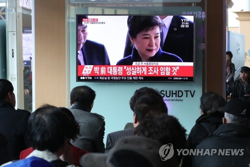 People watch live TV news reports at Seoul Station on March 21, 2017, on former President Park Geun-hye arriving at the Seoul Central District Prosecutors' Office to undergo questioning. (Yonhap)