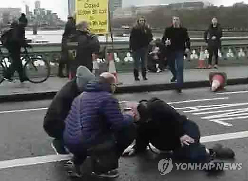 An injured man lies on the road near Britain's Houses of Parliament in London on March 22, 2017. (Yonhap)