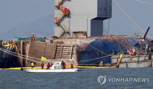 Some family members of the victims killed in the 2014 ferry disaster watch the sunken ship Sewol emerge from the seabed near Jindo, some 472 kilometers south of Seoul, on March 23, 2017. (Yonhap)