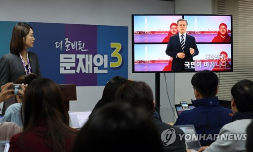 Reporters watch a video clip in which Moon Jae-in, a former leader of the Democratic Party, officially declares his presidential bid, at his office in Seoul on March 24, 2017. (Yonhap)