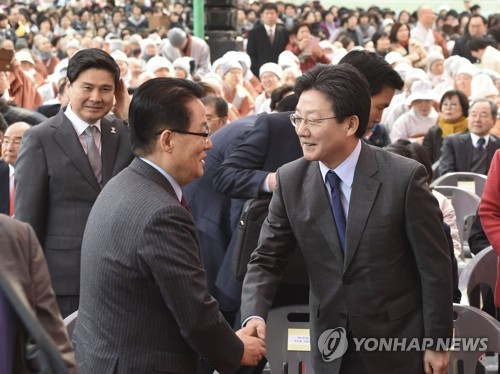Rep. Yoo Seong-min (R) of the conservative Bareun Party shakes hands with Park Jie-won, lawmaker and chief of the centrist People's Party, at a ceremony marking the inauguration of new leadership at the Buddhist Jogye Order in Seoul, South Korea on March 27, 2017. (Yonhap)