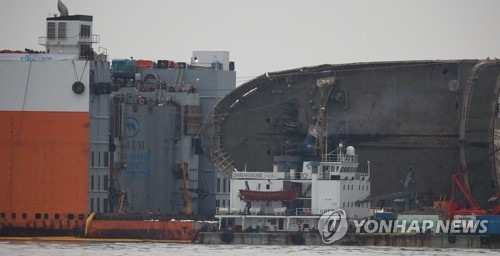 This file photo shows the Sewol ferry being loaded on a semisubmersible transport vessel in waters near Jindo, 472 kilometers southwest of Seoul, on March 26, 2017. The passenger ferry sank on April 16, 2014, killing more than 300 people, mostly high school students on a school trip, in the nation's worst maritime disaster. Nine bodies are still missing. (Yonhap)