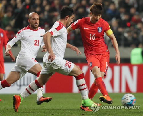 South Korean men's national football team captain Ki Sung-yueng (R) passes the ball against Syrian players during the 2018 FIFA World Cup Asian qualifier between South Korea and Syria at Seoul World Cup Stadium in Seoul on March 28, 2017. (Yonhap)