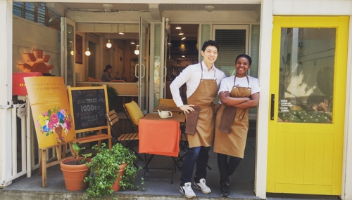 This undated photo offered by Coffee for Tomorrow shows Mun Jun-suk (L), owner of the cafe, posing with one of his African baristas. (Yonhap)