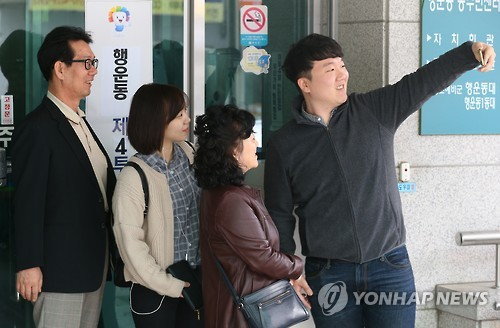 In this file photo, taken on April 13, 2016, a man and his family take a photo in front of a polling booth where they cast their votes in the National Assembly election. Taking photos and sharing them with others to prove or confirm their participation in an election has become sort of a trend among South Koreans, especially the young. (Yonhap)