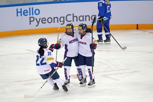 South Korean forward Danelle Im celebrates her goal against Slovenia with teammates Jung Si-yun and Randi Griffin at the International Ice Hockey Federation Women's World Championship Division II
