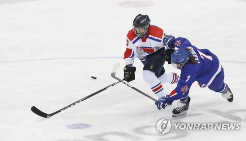 Kim Nong-gum of North Korea battles Georgina Farman of Britain for the puck during their game at the International Ice Hockey Federation Women's World Championship Division II Group A at Gangneung Hockey Centre in Gangneung Gangwon Province