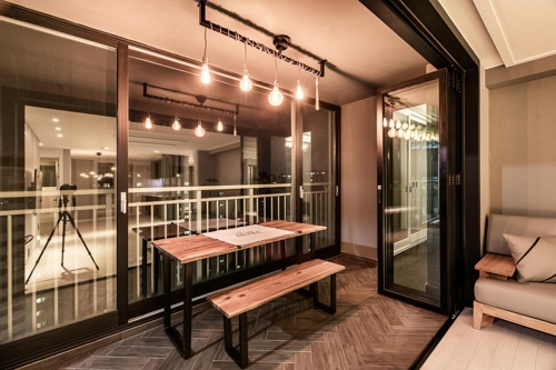 This file photo, provided by Zipdeco, captures a renovated cafe-like balcony of an apartment in Ilsan, north of Seoul, on April 7, 2017. The windows and sliding doors have been redecorated with black frames to match the dark Herringbone wood floor. (Yonhap)