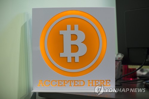 This file photo, released by Europe's news photo agency EPA and dated March 13, 2014, shows a bitcoin sign in the lobby of the ANX office headquarters in Hong Kong, China. (Yonhap)