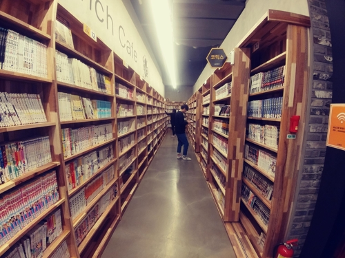 A customer browses comic books in a corridor at Happy Jakdang, a comic book cafe, nearby Hongdae in downtown Seoul. (Yonhap)