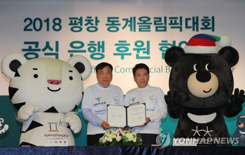 Lee Hee-beom (second from L), head of the 2018 PyeongChang Winter Olympics organizing committee, poses with Ham Young-joo, president of KEB Hana Bank, after the bank became PyeongChang's main banking partner in a signing ceremony in Seoul on April 18, 2017. (Yonhap)