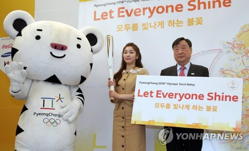 Kim Yu-na, former Olympic figure skating champion and honorary ambassador for the 2018 PyeongChang Winter Olympics, poses with the Olympic torch, flanked by Soohorang (L), the PyeongChang 2018 mascot, and Lee Hee-beom, head of PyeongChang's organizing committee, in Seoul on April 18, 2017. (Yonhap)