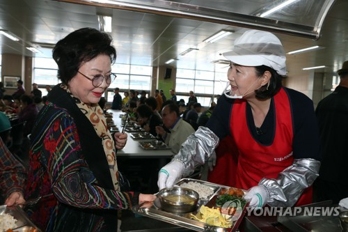 Kim Jung-sook (R), the wife of presidential candidate Moon Jae-in, serves food to the elderly in Gwangju on April 14, 2017. (Yonhap)