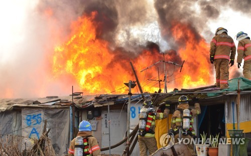 Firefighters try to extinguish the blaze in Guryong Village on March 29, 2017. (Yonhap)