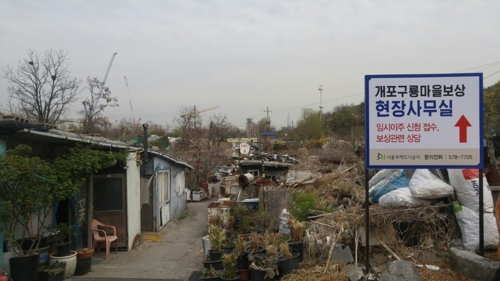 In this photo taken April 13, 2017, the sign says the residents of Guryong Village can apply for temporary housing. (Yonhap)