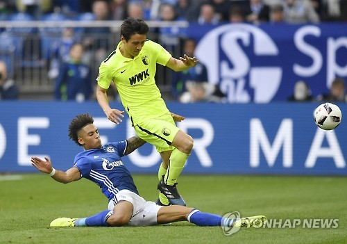 In this Associated Press photo taken on March 12, 2017, Koo Ja-cheol of FC Augsburg (R) is tackled by Thilo Kehrer of FC Schalke 04 during their Bundesliga football match in Gelsenkirchen, Germany. (Yonhap)