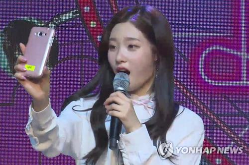 "Chaeyeon, member of South Korean girl group DIA, takes a live video call from a random fan during a media event for the team's new album ""YOLO"" on April 19, 2017, at the Shinhan Card FAN Square in northern Seoul. (Yonhap)"