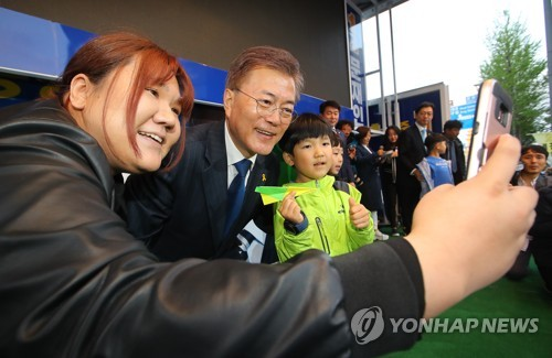 Moon Jae-in (second from L), the presidential candidate of the liberal Democratic Party, poses for a selfie with his young supporters while visiting the southwestern city of Gwangju on April 18, 2017. (Yonhap)