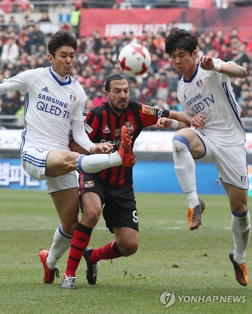In this file photo taken on March 5, 2017, Suwon Samsung Bluewings defenders Lee Jung-soo (L) and Koo Ja-ryong (R) vies for the ball against FC Seoul forward Dejan Damjanovic during their K League Classic match at Seoul World Cup Stadium in Seoul. (Yonhap)