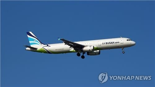 This undated file photo shows an A321-200 jet operated by Air Busan in flight near an airport. (Yonhap)