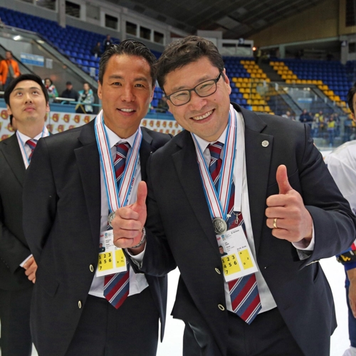 In this photo provided by Hockey Photo, South Korean men's hockey head coach Jim Paek (R) and his assistant Richard Park pose for pictures after South Korea finished in second place at the International Ice Hockey Federation (IIHF) World Championship Division I Group A in Kiev, Ukraine, on April 28, 2017. (Yonhap)